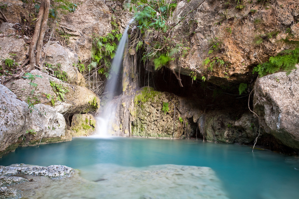 A waterfall cascades down rocks into a pool near a spring providing a rare source of fresh water in Ile de La Gonave, Haiti