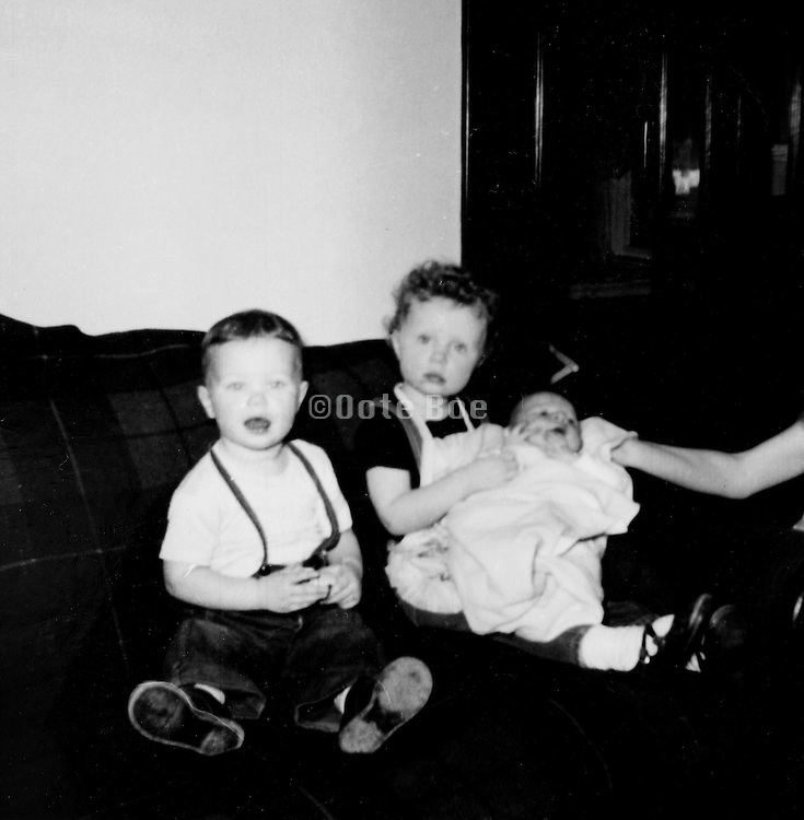 two children posing with new born 1960?s