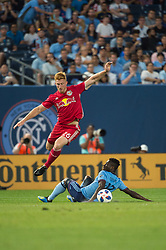 July 8, 2018 - Bronx, New York, United States - New York Red Bulls defender TIM PARKER (26) jumps over a sliding New York City midfielder EBENEZER OFORI (12) during a regular season match at Yankee Stadium in Bronx, NY.  New York City FC defeats the New York Red Bulls 1 to 0 (Credit Image: © Mark Smith via ZUMA Wire)