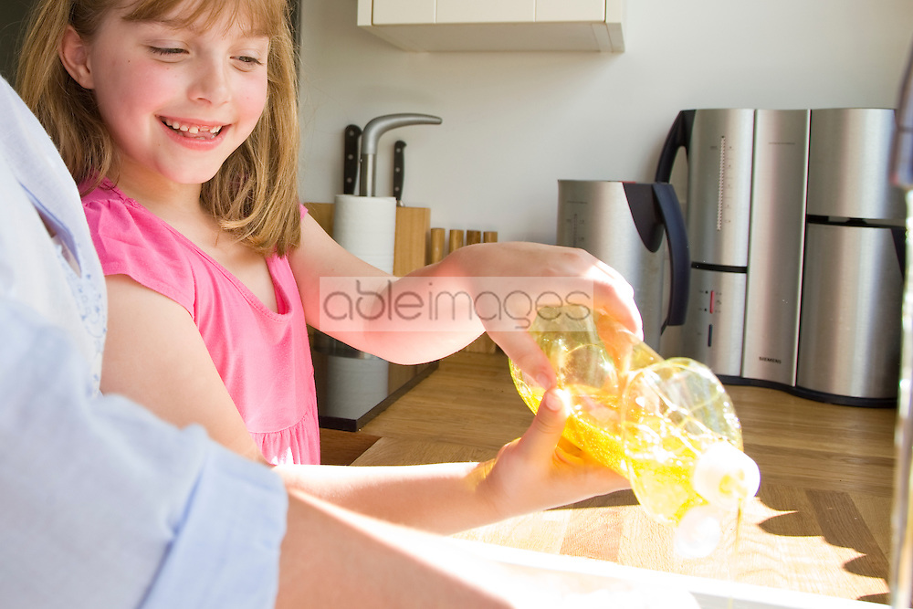 Smiling Girl Squeezing Detergent Bottle