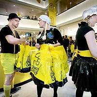 Nederland, Amsterdam , 1 oktober 2009..Personeel verkleed in Oostenrijkse kledij deelt plastic zakken met cadeautjes uit op de eerste etage tijdens de eerste dag van de Drie dwaze Dagen van warenhuis de Bijenkorf..Three Crazy Days, annual sale of the Bijenkorf store, promoting bargains.