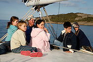 A whalewatching guide telling stories to children during a cruise in Albany.