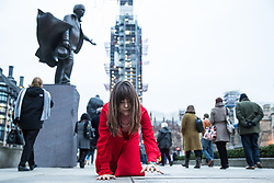 London, UK. 19th January, 2019. A woman wearing a red dress, believed to be artist Ellen Angus, crawls across paving stones around Parliament Square on her hands and knees. Ellen Angus is a member of London-based feminist collective 'Not So Popular' and is understood to have been performing the stunt as part of an upcoming art piece