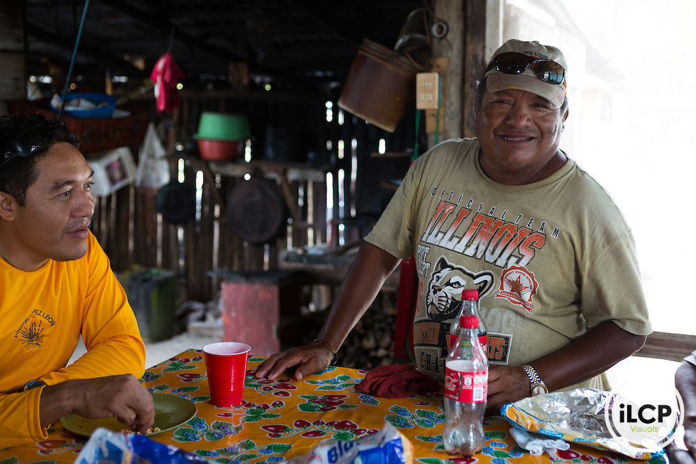 Hilario Salub (right) lives in the La Victoria fish camp, which is actually nothing more than his homestead a 15 minute boat ride from his coorperative's camp, María Elena in the Sian Ka'an Biosphere Reserve in southernmost Caribbean Mexico. Hilario was hosting a group of conventional lobster fishermen from north Progresso, north of Cancun, who wanted to learn about catching the more valuable live lobster using 'casitas cubanas'. From a 2014 iLCP (International League of Conservation Photographers) expedition project documenting the people and places of the Mexican section of the Mesoamerican Reef (MAR).