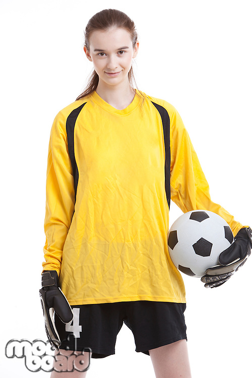 Portrait of young female soccer player with ball against white background