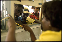 CAP HAITIEN, HAITI - People crowd the pharmacy window at Cap Haitien's only hospital where medication is in short supply and almost impossible to get, even for those who can afford it. (PHOTO © JOCK FISTICK)....