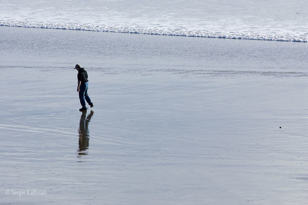 A young couple and their dog playing on  a beach at the Ecola State Park in Oregon in the Spring