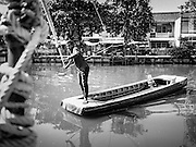 16 FEBRUARY 2017 - THEPHARAK, SAMUT PRAKAN, THAILAND: A boatman pulls his small boat, which he uses as a ferry, across Khlong Samrong, in the Bangkok suburbs. The boatman pulls it across using a system of ropes and pulleys. He's been working on the boat since he was a child. Small ferries like this used to be common in Bangkok but many of the khlongs (the canals that used to crisscross Bangkok) have been filled in and bridges have been across the remaining khlongs. Now there are only a handful of the ferries left. This ferry charges 2 Baht (the equivalent of about .06¢ US) per person to take a person across the khlong.      PHOTO BY JACK KURTZ