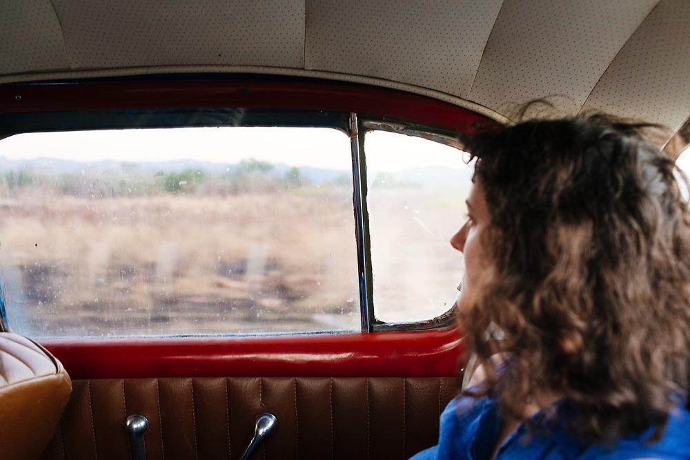 Twenty something looks out the window of a 50's car in Trinidad, Cuba
