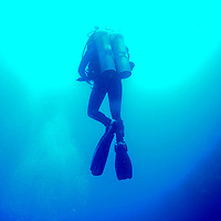 "A scuba diver ascends inside the Blue Hole in Dahab, Egypt. The Blue Hole is notorious for the number of diving fatalities which have occurred there, earning it the sobriquet ""World's Most Dangerous Dive Site"" and the nickname ""Diver's Cemetery"". The site is signposted by a sign that says ""Blue hole: Easy entry"". Accidents are frequently caused when divers attempt to find the tunnel through the reef (known as ""The Arch"") connecting the Blue Hole and open water at about 52 m depth. According to dive experts roughly 10 people die each year. April 2012."