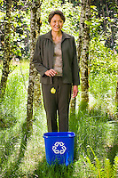 A mature Asian businesswoman standing in a green forest dropping a piece of paper into a recycle bin.