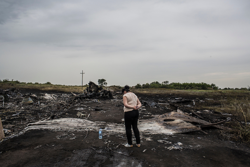 GRABOVO, UKRAINE - JULY 18: A woman looks at the wreckage of a passenger plane brought down by a missle the previous day on July 18, 2014 in Grabovo, Ukraine. Malaysia Airlines flight MH17 travelling from Amsterdam to Kuala Lumpur has crashed on the Ukraine/Russia border near the town of Shaktersk. The Boeing 777 was carrying 280 passengers and 15 crew members. (Photo by Brendan Hoffman/Getty Images) *** Local Caption ***