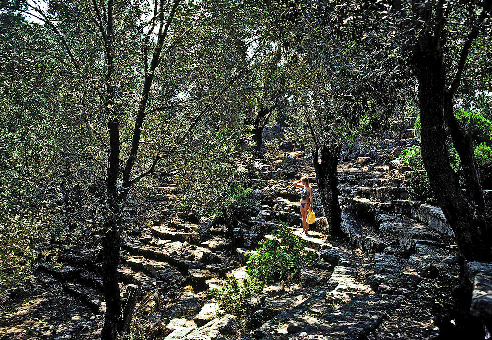 Exploring a remote, unexcavated Hellenistic odeon somewhere near ancient Cnidos in Turkey.  Young woman in a blue bikini stands looking around in a patch of sunlight filtered through the trees.