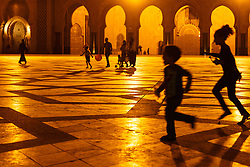 People on grand plaza in front of Hassan II Mosque at night,, Casablanca, Morocco