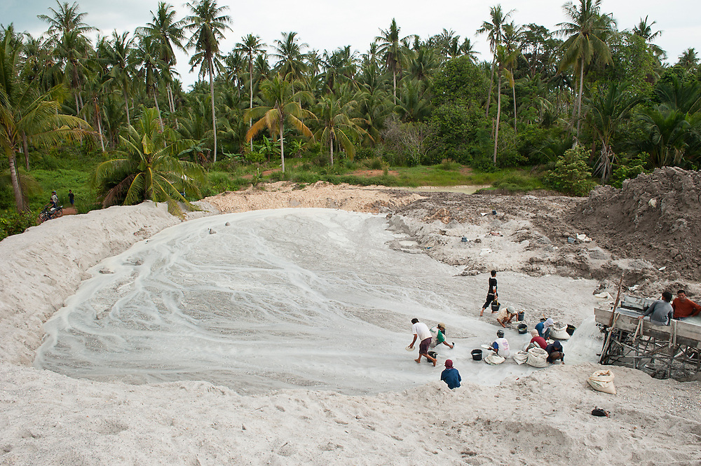 The hidden side of high tech smartphones. Miners sift sand in seach of tin in an illegal tin mine in Reboh, Bangka island, Indonesia. The demand for tin has increased due to its use in smart phones and tablets. Thousands of miners from all over Indonesia come to Bangka Island (Indian Ocean), to work under hard circumstances in illegal and dangerous tin mines. Bangka Island is devastated by illegal tin mines.<br /> <br /> Le côté caché du succès des smartphones. Mineurs tamisent du sable dans une Mine d'étain illégale à Reboh, L'île de Bangka (Indonésie) est dévastée par des mines d'étain sauvages. Des milliers de mineurs de toute l'Indonésie viennent à l'île de Bangka (océan Indien), pour travailler dans des conditions difficiles dans les mines d'étain illégales et dangereuses. La demande de l'étain a explosé à cause de son utilisation dans les smartphones et tablettes.