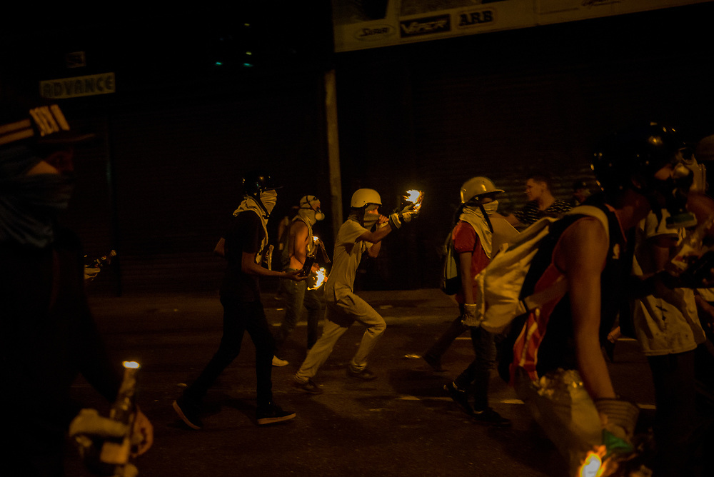 CARACAS, VENEZUELA - MAY 8, 2017:  Anti-government protesters chase security forces, while throwing molotov cocktails at them. The streets of Caracas and other cities across Venezuela have been filled with tens of thousands of demonstrators for nearly 100 days of massive protests, held since April 1st. Protesters are enraged at the government for becoming an increasingly repressive, authoritarian regime that has delayed elections, used armed government loyalist to threaten dissidents, called for the Constitution to be re-written to favor them, jailed and tortured protesters and members of the political opposition, and whose corruption and failed economic policy has caused the current economic crisis that has led to widespread food and medicine shortages across the country.  Independent local media report nearly 100 people have been killed during protests and protest-related riots and looting.  The government currently only officially reports 75 deaths.  Over 2,000 people have been injured, and over 3,000 protesters have been detained by authorities.  PHOTO: Meridith Kohut