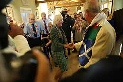 The Prince of Wales and the Duchess of Cornwall, known as the Duke and Duchess of Rothesay in Scotland, have a dance during a visit to Dumfries House garden party and dog show, in Cumnock, Scotland.