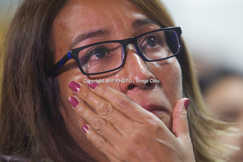 Isabel Medina, 41, a non U.S. citizen, wipes her eye as she is watching a television broadcast of President Barack Obama's speech on immigration, in Los Angeles, California on November 20, 2014. AFP PHOTO / Ringo Chiu