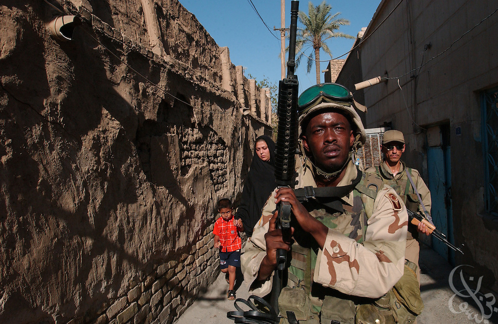 U.S. Army 3rd Battalion 124th Infantry Florida National Guard Specialist Mungai Kinya, from Miramar, Florida moves on point through a narrow alley while on a September 17, 2003 joint patrol with newly trained members of the Iraqi Civil Defense Corps (ICDC) in the Al-Kesra district of Baghdad, Iraq.