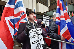 © Licensed to London News Pictures. 08/04/2018. LONDON, UK. A man holds a sign and a flag at a protest calling for Jeremy Corbyn, leader of the Labour party, to be held to account.  The event was organised by the Campaign Against Anti-Semitism, outside the Labour Party's headquarters in central London.  Photo credit: Stephen Chung/LNP