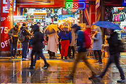 London, December 31 2017. The umbrellas come out as a downpour begins in London's west end ahead of the New Year's Eve fireworks at midnight. PICTURED: People rush through the rain on Piccadilly. © SWNS