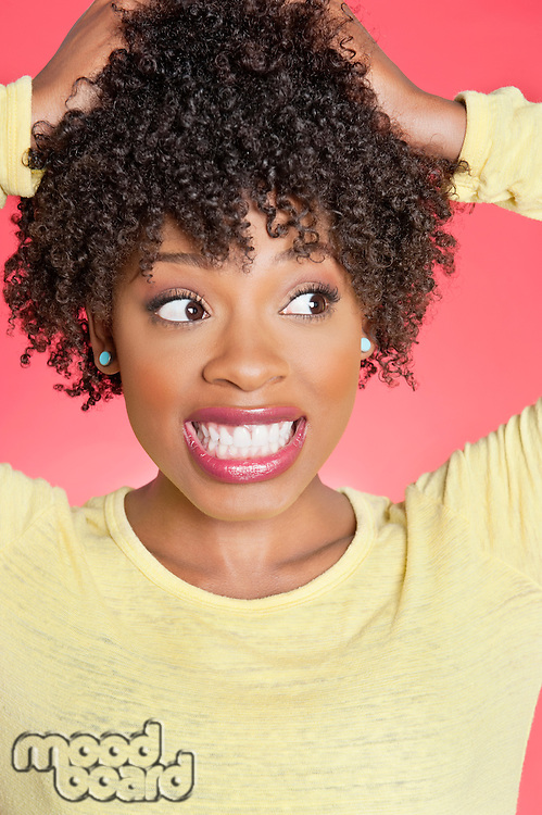 African American looking sideways with hands in hair over colored background
