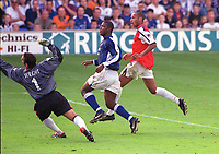 Thierry Henry (Arsenal) chips the ball over Richard Wright and Titas Bramble (Ipswich). F.A.Carling Premiership, 23/9/2000. Credit: Colorsport / Stuart MacFarlane.
