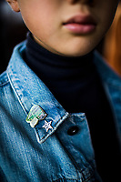 A young boy who follows the Seven Stars Kyushu luxury train in Japan from station to station on weekend, wearing train pins on his jean jacket.