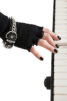 Close-up of female hands with fingerless gloves and bracelet playing piano keyboard