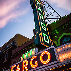 Photo of Fargo Theater and marquee sign at night in Fargo, North Dakota. The sunset provided colorful purple and pink sky and cloud colors. The Fargo Theatre was built in 1926 and is on the National Register of Historic Places. The Fargo Theatre is currently a popular venue for films, movies, concerts, plays and other live events. Photo is vertical and was taken in 2011.