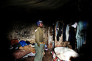 Rosarno, Italia - 19 dicembre 2010. Un immigrato all'interno della sua stanza nella casa abbandonata in cui vive a Rosarno..Ph. Roberto Salomone Ag. Controluce.ITALY - An immigrant inside his house in Rosarno on December 19, 2010.