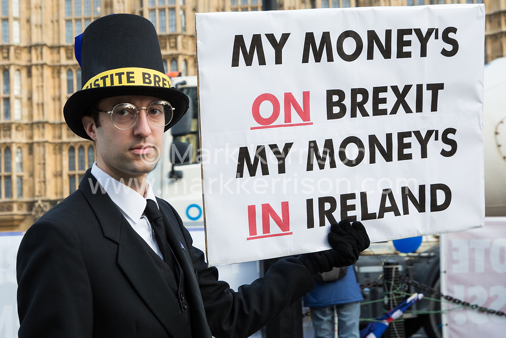 London, UK. 9th January, 2019. An anti-Brexit activist disguised as Jacob Rees-Mogg and carrying a sign reading 'My Money's on Brexit My Money's in Ireland' protests with pro-EU group SODEM (Stand of Defiance European Movement) outside Parliament on the first day of the debate in the House of Commons on Prime Minister Theresa May's proposed Brexit withdrawal agreement.
