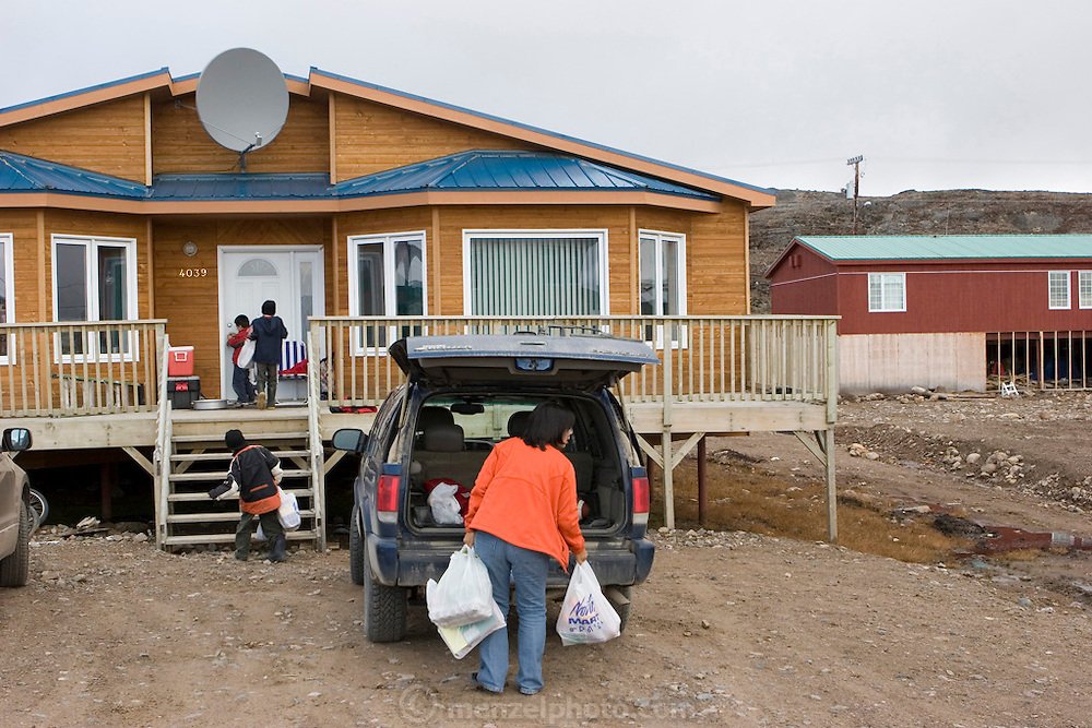 "Pauline Melanson unloading groceries in front of her family home, in Iqaluit, Nunavut, Canada. The Melanson family consists of Peter, Pauline, Joseph, Jacob, and Shane. They live one street off ""The Road To Nowhere,"" on a hill overlooking the town of Iqaluit in Canada's northeastern territory of Nunavut (just south of the Arctic Circle)."