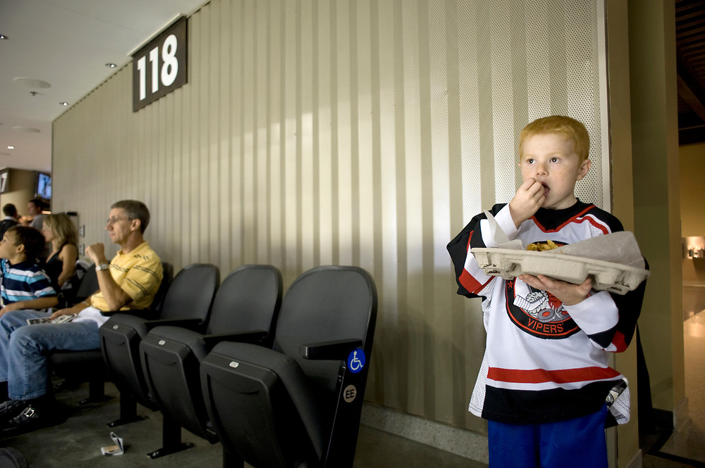 Shane Miller, age 7, of Tarentum, eats french fries while taking in the new Consol Energy Center before a Pittsburgh Penguins Preseason hockey game.