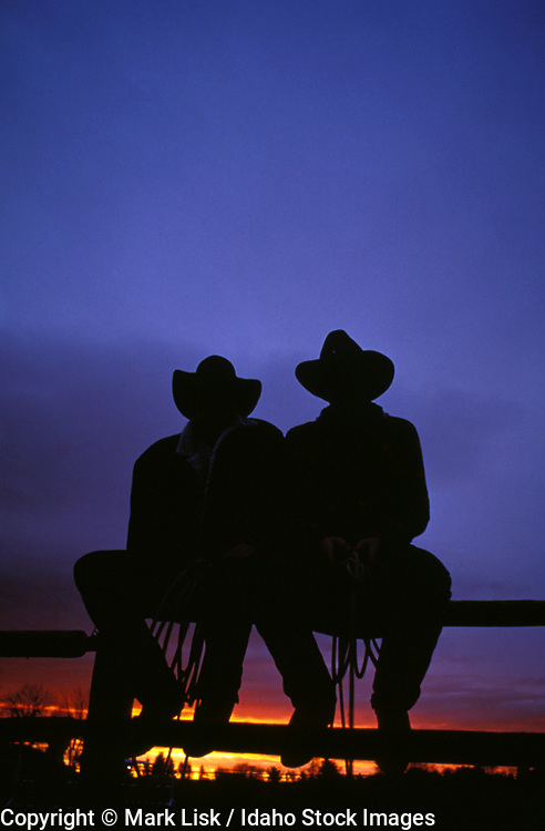 THIS PHOTO IS AVAILABLE FOR WEB DOWNLOAD ONLY. PLEASE CONTACT US FOR A LARGER PHOTO. Two cowboys sitting on a fence silhouetted against a beautiful sunset sky.  MR