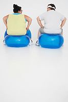 Overweight man and woman Resting on Exercise Balls back view