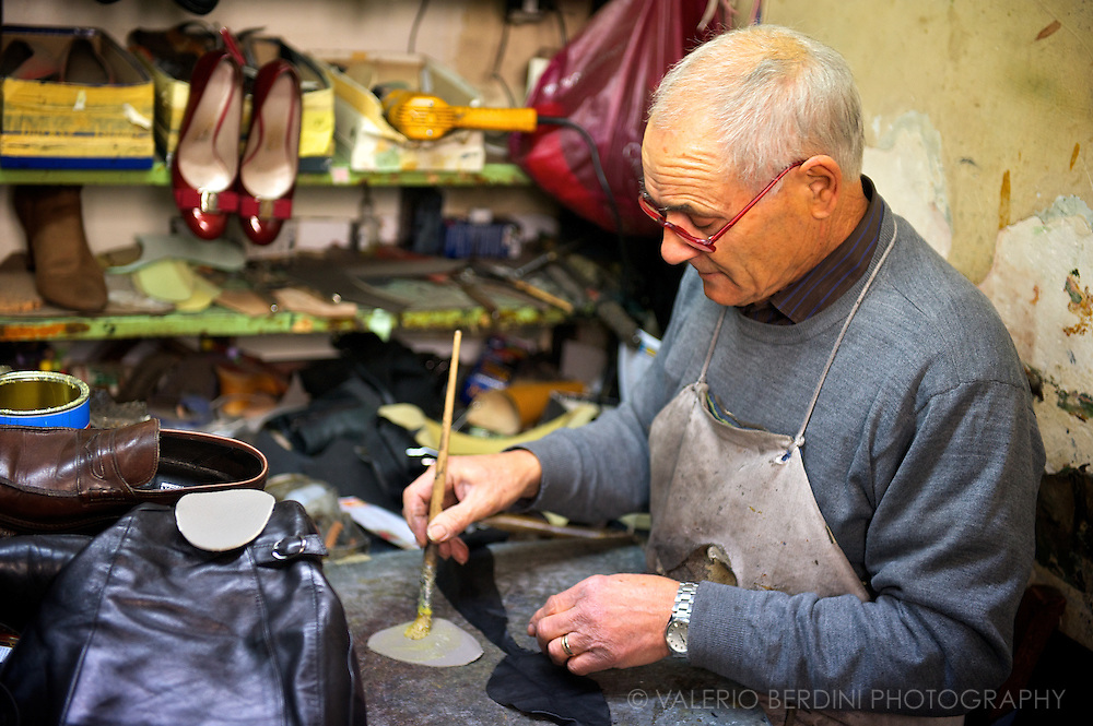 The cobbler takes minutes to stick an additional sole in the larger of the two shoes.