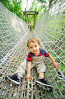 A young boy enjoys a suspension bridge high in the forest canopy at one of Sapporo's most popular parks.