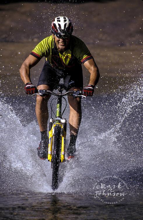 Mountain biker splashing through stream, Kauai, Hawaii