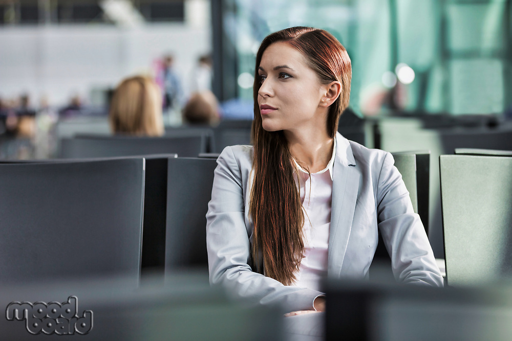 Portrait of young attractive businesswoman sitting while waiting in her gate for boarding at airport