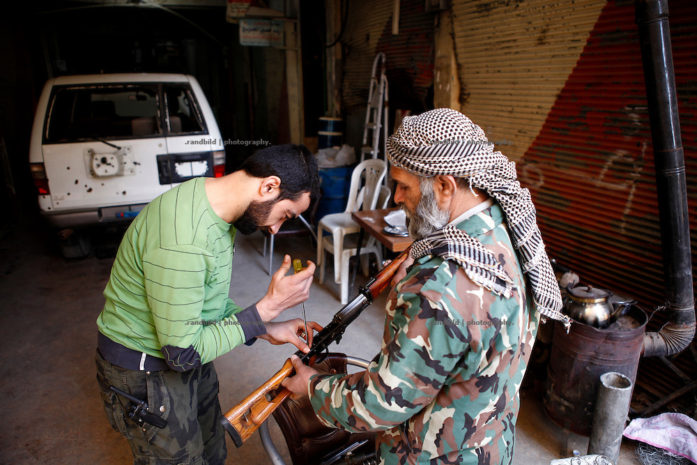 Two FSA fighters fixing a sniper rifle in the morning. Residents of eastern syrian town Deir az-Zor joined arab spring protests against the regime of Bashar al-Assad from its early beginning in March 2011. Since summer 2012 the town with few hundred thousand inhabitants is embattled between the Syrian Army and different opposing rebel groups like Free Syrian Army and Jabhat al-Nusra. Deir az-Zor is target to constant shelling by artillery, war planes and short range missiles. Almost 70 percent of the town is rebel held while government forces remain in control over some residental areas and a strategic important airport. Deir az-Zor is widely damaged and some areas almost totally destroyed by fierce and long lasting battles. All direct road connections to Deir az-Zor are cut and fighters and returning residents as well depend on one provisional supply line across the Euphrates river which is regularly targeted by government snipers.