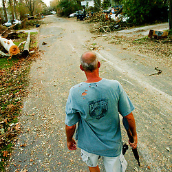 Kyle Green | The Roanoke Times<br /> September 01, 2005  Gulfport Mississippi resident, Billy Bova patrols his neighborhood with a 12 gauge shotgun eight days after Hurricane Katrina. The neighborhood where Billy and his girlfriend own a house in suffered extensive damage. Power and water are still out, and gunshots have been heard in the area in recent nights. Billy said that Gulfport Police have told him that he should be prepared to defend himself and his property.