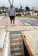 Ed Thomas, of Parkersburg, a teacher and football coach at Aplington-Parkersburg High School stands at the top of the stairs looking into his basement where he and his wife took cover during the tornado in Parkersburg, Iowa on Wednesday June 4, 2008. The Thomas' house was totally destroyed. (Stephen Mally for the New York Times)