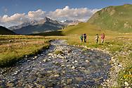 Wandergruppe auf der Via Sett bei der Ebene Plang da Camfer mit dem Bach Eva dal Sett nördlich des Septimerpasses an einem schönen Sommertag im August