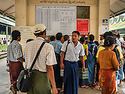 26 OCTOBER 2015 - YANGON, MYANMAR: Passengers line up to buy tickets for the Yangon Circular Train. The Yangon Circular Railway is the local commuter rail network that serves the Yangon metropolitan area. Operated by Myanmar Railways, the 45.9-kilometre (28.5mi) 39-station loop system connects satellite towns and suburban areas to the city. The railway has about 200 coaches, runs 20 times daily and sells 100,000 to 150,000 tickets daily. The loop, which takes about three hours to complete, is a popular for tourists to see a cross section of life in Yangon. The trains run from 3:45 am to 10:15 pm daily. The cost of a ticket for a distance of 15 miles is ten kyats (~nine US cents), and for over 15 miles is twenty kyats (~18 US cents).    PHOTO BY JACK KURTZ