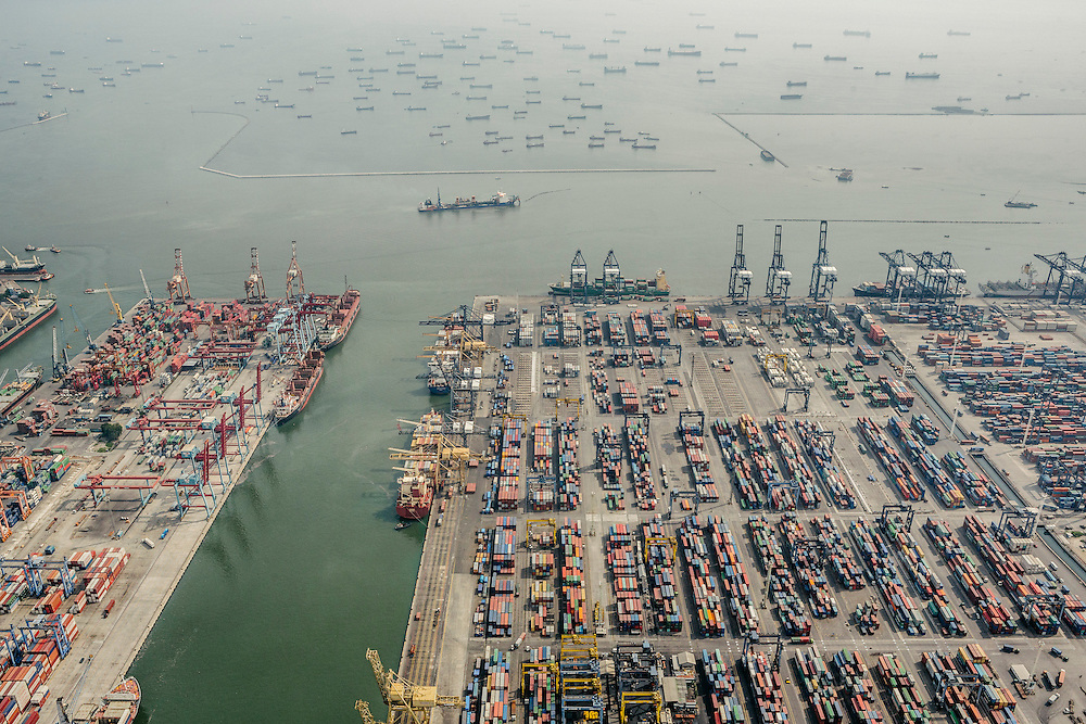 Ships waiting to dock at the the port. The Port of Jakarta also known as Tanjung Priok Port is the largest Indonesian seaport and one of the largest seaports in the Java Sea basin, with an annual traffic capacity of around 45 million tonnes of cargo and 4,000,000 TEU's.This port is located in Tanjung Priok, North Jakarta.
