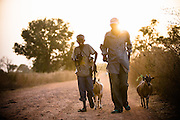 Father and son walking goats down road. Oumar Diao, Father. Hamadou Diao, 10yrs. Kandiaye Village.