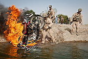 Marines destroy a motorcycle captured from insurgents.