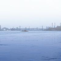 View down the East River towards Manhattan Bridge on a foggy day. Manhattan, New York City.