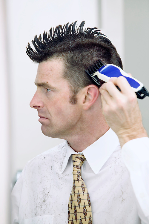 Businessman cutting his hair with clippers.